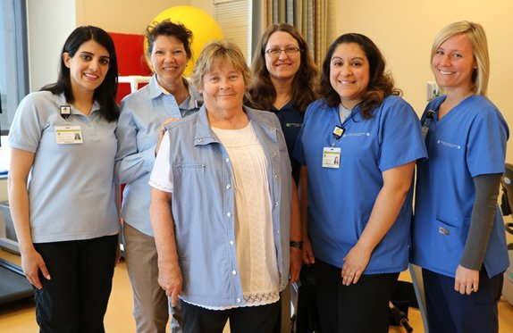Kathy Albert stands with a smiling team of rehabilitation therapists.