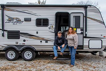 Husband and wife outside camping trailer