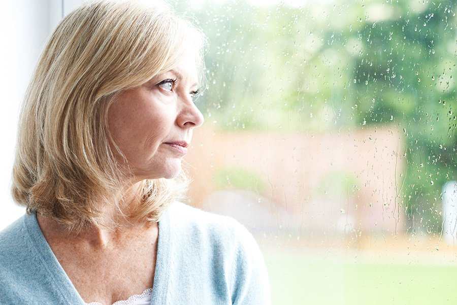 Woman looking out window depressed